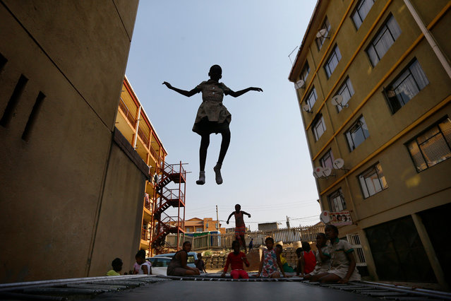 """A school girl hangs in mid air as if flying as she jumps on one of the three trampolines at the Alexandra Trampoline Club after school in the impoverished township in Johannesburg, South Africa, 06 September 2017. Despite being one of the poorest urban areas in the country, the Alexandra Township or """"Alex"""" today is a vibrant and colorful township with a lively atmosphere. Alex was once the home of late Nelson Mandela, when he was studying at the University of South Africa. Children play soccer in the streets between shacks, with open sewers running nearby, as others spend their leisure time on an open field of dirt. Meanwhile, other children have found entertainment as they gather to play on trampolines. The new activity can be seen in Alex as twisting bodies, from the Alexandra Township Trampoline Club, jump on huge trampolines set between two blocks of flats. Hudson Nxumalo, the coach of the Alexandra Trampoline Club, has produced some stars already like regional champion Phaphama Nxumalo (13). Six gymnasts of the Alexandra Trampoline Club have been selected to represent South Africa at the 2014 Indo Pacific Championships. (Photo by Kim Ludbrook/EPA/EFE)"""