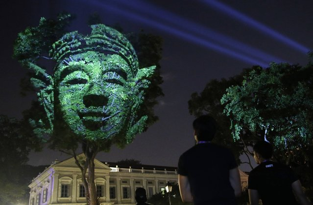 "People look at French artist Clement Briend's photographic light installation ""Divine Trees"", which features images of divine figures highly revered in Asian cultures projected on trees towering over bystanders, during a media preview of the Singapore Night Festival in Singapore August 21, 2014. The Singapore Night Festival begins on Friday. (Photo by Edgar Su/Reuters)"