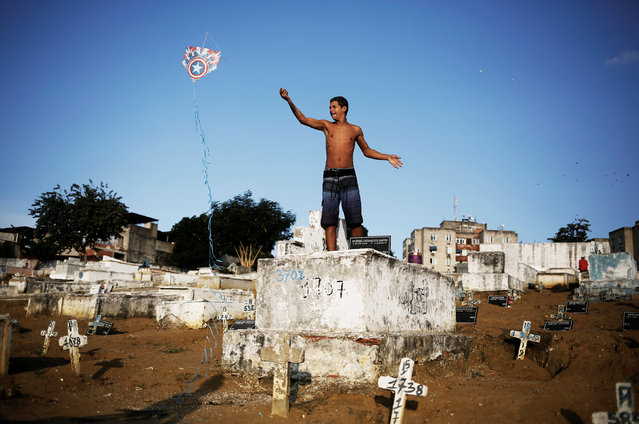 A man flies his kite in a cemetery in the Vila Operaria Favela of Rio de Janeiro, Brazil, June 25, 2016. (Photo by Nacho Doce/Reuters)