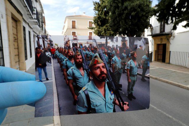 A Reuters photographer holds a picture of Spanish legionnaires marching before a procession taken in April, 2019, in front of the street of the procession, on Palm Sunday, the first day of Holy Week, amid the coronavirus disease (COVID-19) outbreak, in Ronda, southern Spain, April 5, 2020. (Photo by Jon Nazca/Reuters/Illustration)