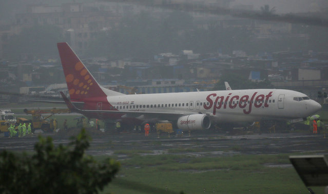 A domestic Spice Jet aircraft is seen off the runway after it skidded off into the unpaved surface during heavy rains in Mumbai, India, Wednesday, September 20, 2017. (Photo by Rafiq Maqbool/AP Photo)