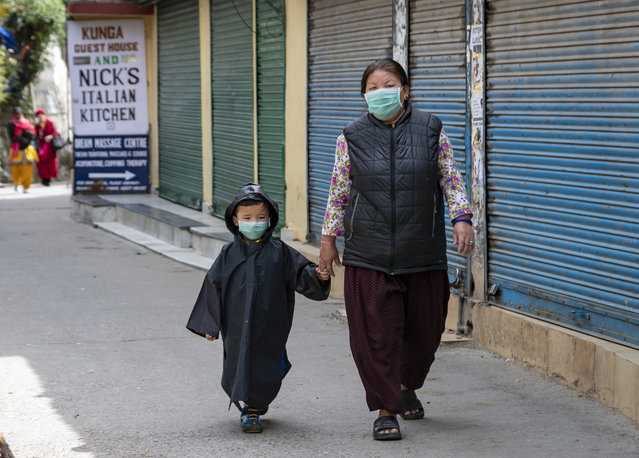 A child is covered in a raincoat and mask to protect him from coronavirus infection as he walks with an adult in Dharmsala, India, Monday, April 20, 2020. India recorded its biggest single-day spike in coronavirus cases on Monday as the government eased one of the world's strictest lockdowns to allow some manufacturing and agricultural activity to resume. (Photo by Ashwini Bhatia/AP Photo)