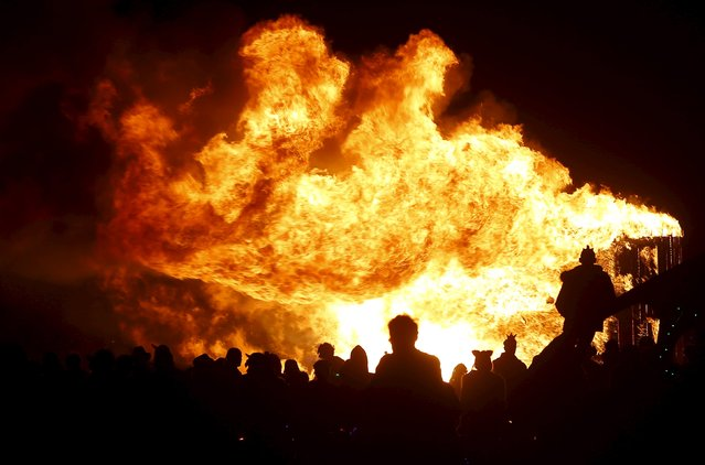 """Participants gather to watch an art installation burn during the Burning Man 2015 """"Carnival of Mirrors"""" arts and music festival in the Black Rock Desert of Nevada, September 3, 2015. (Photo by Jim Urquhart/Reuters)"""