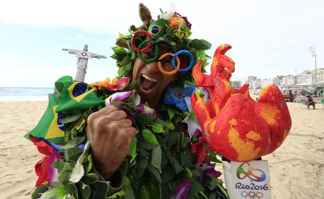 A man dressed in leaves and animals of the forest, the Redeemer on his shoulder, holding the Olympic torch and wearing Olympic rings glasses walks along Copacabana Beach, Rio de Janeiro, Brazil, 31 July 2016. The 2016 Olympic Games start on 05 August. (Photo by Barbara Walton/EPA)