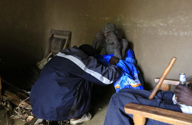 A traditional Bukusu circumciser checks on the condition of a youth who just underwent circumcision inside a house in Kenya's western region of Bungoma August 8, 2014. (Photo by Noor Khamis/Reuters)