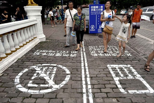 In this photo taken Saturday, September 13, 2014, residents walk on a lane painted with instructions to separate those using their phones as they walk from others in southwest China's Chongqing Municipality. The Chinese city took a cue from a U.S. TV program and created a sidewalk with a separate lane for those with heads tucked into smartphones, as a reminder not to tweet while walking the street. (Photo by AP Photo)