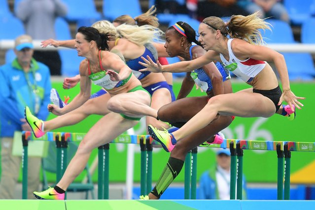 Hungary's Gyorgyi Zsivoczky-Farkas (L) competes in the Women's Heptathlon 100m Hurdles during the athletics event at the Rio 2016 Olympic Games at the Olympic Stadium in Rio de Janeiro on August 12, 2016. (Photo by Franck Fife/AFP Photo)