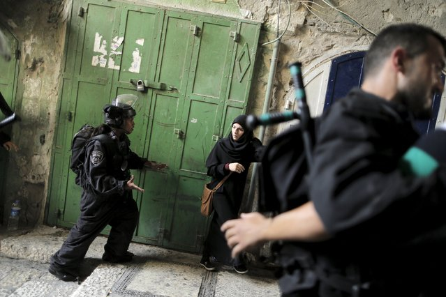 An Israeli policewoman prevents a Palestinian woman from entering the compound which houses al-Aqsa mosque, known by Muslims as the Noble Sanctuary and by Jews as the Temple Mount, in Jerusalem's Old City September 13, 2015. (Photo by Ammar Awad/Reuters)