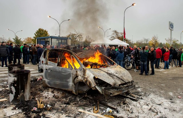 A car burns as workers block the main gate of the Ford plant in Genk, Belgium October 25, 2012. Ford Motor Co. announced Wednesday it planned to close a car plant in eastern Belgium – one of its main European factories – by the end of 2014, a move that would result in 4,500 direct job losses and 5,000 more among subcontractors. (Photo by Geert Vanden Wijngaert/Associated Press)