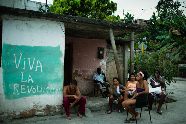 Neighbors in the poor neighborhood of Portuondo in Santiago, Cuba sit by mural that translates to Long Live the Revolution. (Photo by Sarah L. Voisin/The Washington Post)