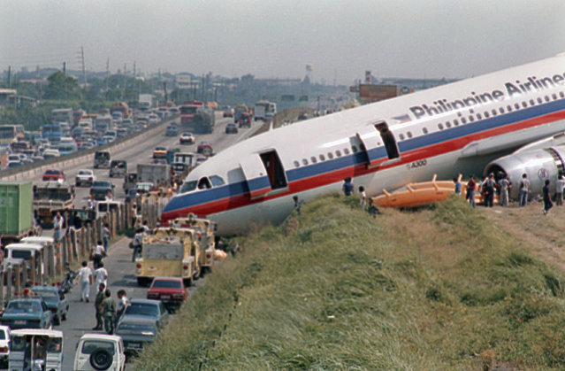 A Philippine Airlines A300 Airbus plane lies near the service road of a highway south of Manila after it overshot the runway, September 19, 1987 in Manila upon landing from Singapore. Nobody was injured among 135 passengers and crewmen on board. (Photo by Bullit Marquez/AP Photo)