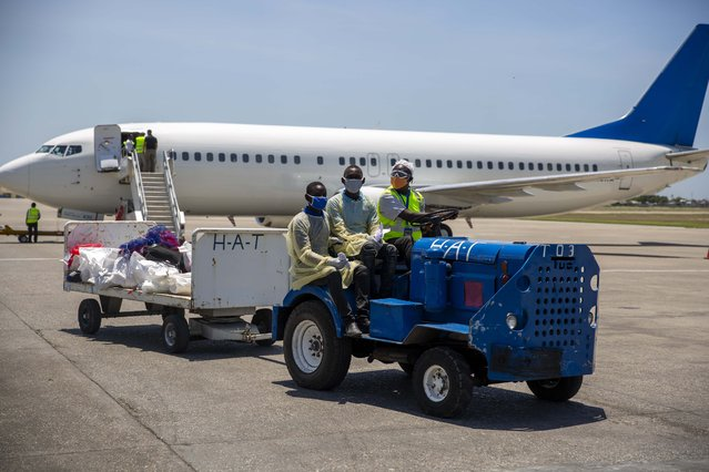 Airport workers, wearing protective face masks and gowns, transport the bags of arriving Haitians who were deported from the United States, at the Toussaint Louverture International Airport in Port-au-Prince, Haiti, Tuesday, May 26, 2020. (Photo by Dieu Nalio Chery/AP Photo)