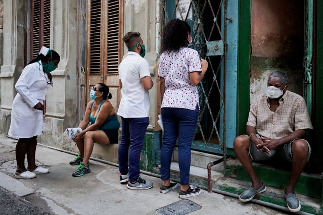 Medical students check door to door for people with symptoms amid concerns about the spread of the coronavirus disease (COVID-19), in downtown Havana, Cuba, May 11, 2020. (Photo by Alexandre Meneghini/Reuters)