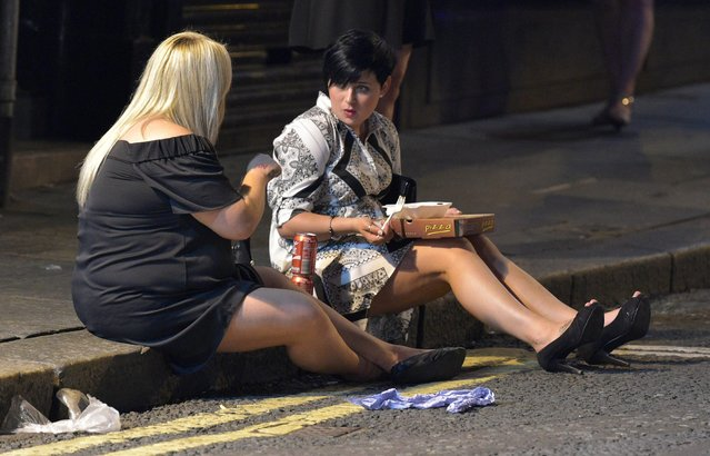 Two friends tuck into their takeaway while gossiping on the pavement. Mayhem hits the streets of Newcastle, UK as clubbers out on the Toon have a little too much to drink as they enjoy the Bank Holiday on August 29, 2016. Photographs take last night show scantily-clad women passed out on the pavement, while boozed-up men were caught arguing with police. (Photo by XposurePhotos.com)