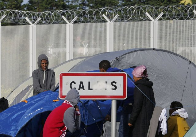 "Migrants stand near a Calais city sign along a road near the makeshift camp called ""The New Jungle"" in Calais, France, September 19, 2015. (Photo by Regis Duvignau/Reuters)"