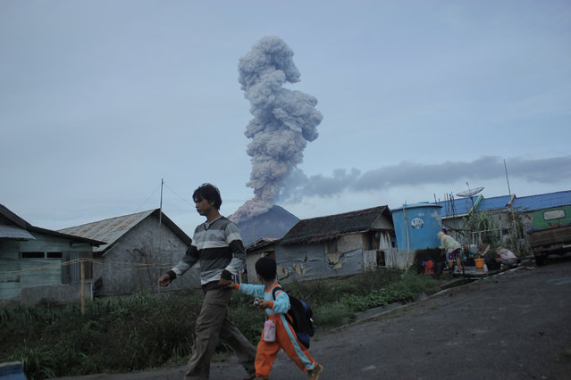 A villager holds a child and walk as Mount Sinabung spews volcanic ash into the air during an eruption in Karo, North Sumatra, Indonesia, September 3, 2016. (Photo by Zulkarnain Ginting/Reuters/Antara Foto)