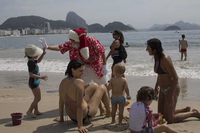 Paulo Mourao, 67, high fives with a kid as he performs as Santa Claus at Copacabana beach in Rio de Janeiro, Brazil, Thursday, December 21, 2017. Mourao went to the beach as a Santa Claus surfer to celebrate the beginning of Summer in the southern hemisphere. (Photo by Leo Correa/AP Photo)