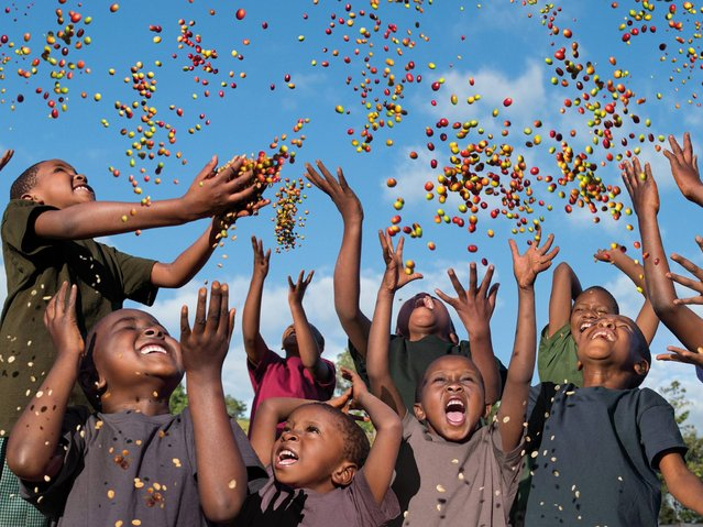 """""""Future in Our Hands"""". Children in Father Peter's School in Tanzania who symbolise the Earth Defenders of the future, throwing colourful coffee seeds into the air demonstrates that the future really does lie in our own hands. (Photo by Steve McCurry/2015 Lavazza Calendar)"""
