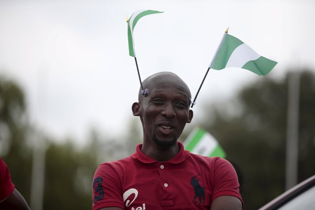 A man, with two flags of Nigeria stuck to his head, reacts as he takes part in celebrations for the country's 55th Independence Day in Abuja, Nigeria, October 1, 2015. (Photo by Afolabi Sotunde/Reuters)