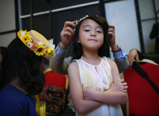 A staff adjusts a hair pin on a child model at the backstage during a rehearsal for the Dong Wenmei T100 Children's Collection during China Fashion Week in Beijing October 29, 2014. (Photo by Kim Kyung-Hoon/Reuters)