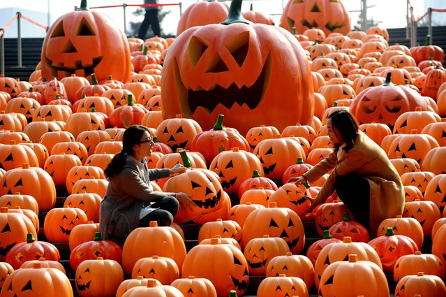 Visitors pose for photos in an installation consists of 500 pumpkin lights to mark the Halloween in Shenyang, northeast China's Liaoning province on October 29, 2014. This year's Halloween will fall on Friday, October 31, 2014. (Photo by AFP Photo/Stringer)