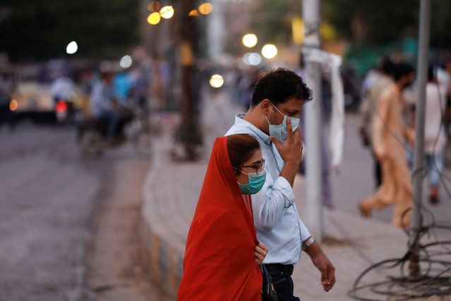 A man and woman wear protective masks while walking along a street after Pakistan lifted lockdown restrictions, as the coronavirus disease (COVID-19) outbreak continues, in Karachi, Pakistan on August 18, 2020. (Photo by Akhtar Soomro/Reuters)
