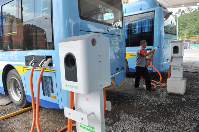 In this Friday, July 15, 2016, photo, a driver charges an electric bus made by King Long United Automotive Industry at a terminal in Lin'an city in eastern China's Zhejiang Province. China's electric vehicle industry, a flagship for Beijing's technology ambitions, has been rocked by scandal after five companies were caught collecting millions of dollars in subsidies for buses they never made. (Photo by Chinatopix via AP Photo)