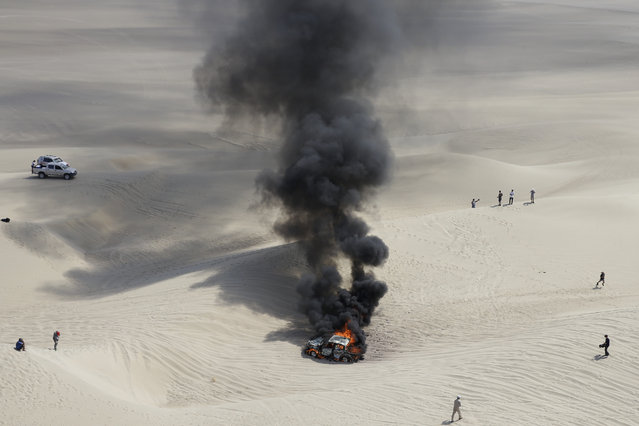 The Toyota of driver Alicia Reina and co-driver Carlos Dante Pelayo, both of Argentina, burns after catching fire during the third stage of the 2018 Dakar Rally in Pisco, Peru, Monday, January 8, 2018. (Photo by Ricardo Mazalan/AP Photo)