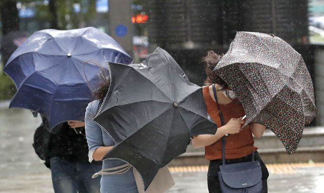 People struggle with their umbrellas against strong wind and rain in downtown Seoul, South Korea, Thursday, September 3, 2020. A powerful typhoon ripped through South Korea's southern and eastern coasts with tree-snapping winds and flooding rains Thursday, knocking out power to thousands of homes. (Photo by Lee Jin-man/AP Photo)