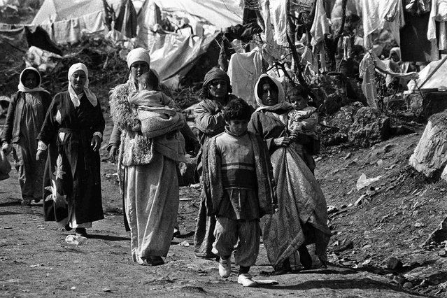 Iraqi Kurdish women carry their children in the Cukurca refugee camp in Turkey April 8, 1991. (Photo by Srdjan Zivulovic/Reuters)
