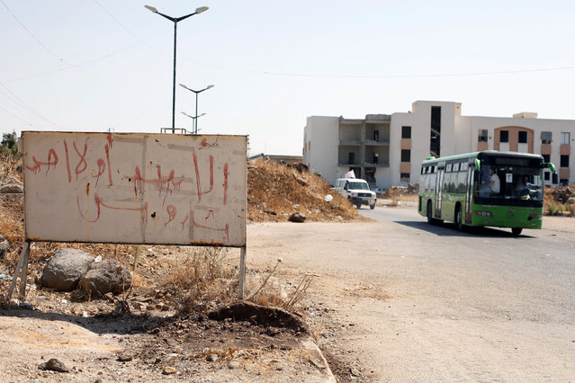 """A bus with Syrian rebels and their families evacuating the besieged Waer district in the central Syrian city of Homs is pictured after a local agreement reached between rebels and Syria's army, Syria, September 22, 2016. The graffiti on the sign reads in Arabic: """"Assad or nobody, only Bashar"""". (Photo by Omar Sanadiki/Reuters)"""