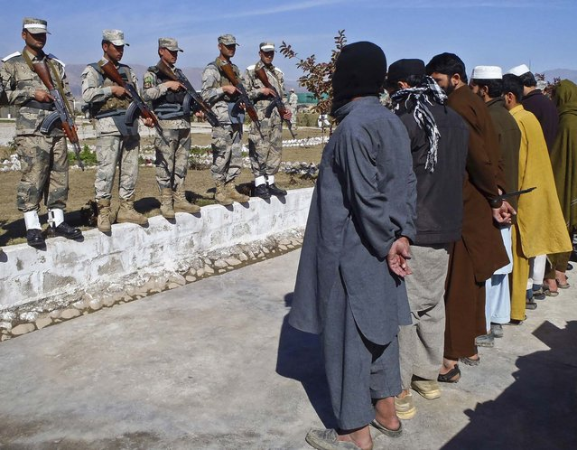 Taliban militants, who were arrested by Afghan border police, stand handcuffed as they are presented to the media at the Afghan border police headquarters in Jalalabad, March 2, 2013. (Photo by Rahmat Gul/Associated Press)
