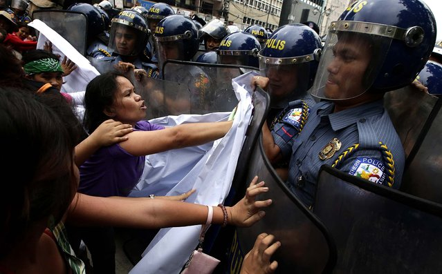 Protesters clash with police as they try to march closer to the US Embassy in Manila to commemorate International Women's Day. Thousands of Filipinos commemorated Women's Day with calls to stop violence against women and children. (Photo by Bullit Marquez/Associated Press)