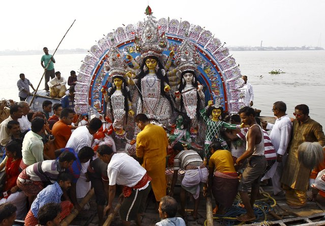 Devotees load an idol of Hindu goddess Durga onto a boat as it is being transported for immersion in the waters of the river Ganges on the last day of the Durga Puja festival in Kolkata, India, October 22, 2015. (Photo by Rupak De Chowdhuri/Reuters)