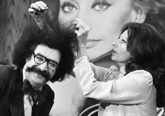 "Actress Sophia Loren teases the hair of critic Gene Shalit in New York, Tuesday, February 20, 1979. During the filming of a segment for the NBC television ""Today"" show. In the background is a large photograph of Miss Loren. The segment is scheduled for airing later this week. (Photo by Dave Pickoff/AP Photo)"