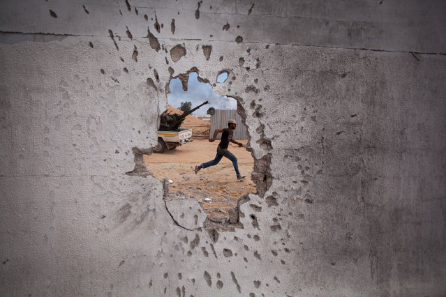 Manu Brabo was born in Spain in 1981. After studying Photography in The School of Arts and Crafts in Oviedo, he moved to Madrid where he started Journalism in Carlos III University while he was working as a photographer for several humble newspapers and agencies. Here: a Libyan revolutionary fighter runs for cover while attacking pro-Gadhafi forces in Sirte, Libya, Friday, October 7, 2011. (Photo by Manu Brabo/AP Photo)