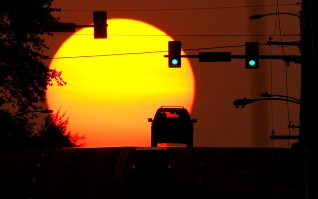 A car is silhouetted against the setting sun, Sunday, September 20, 2020, in Shawnee, Kan. Sunsets have been more vibrant than normal recently as smoke from western wildfires drifts across the United States. (Photo by Charlie Riedel/AP Photo)