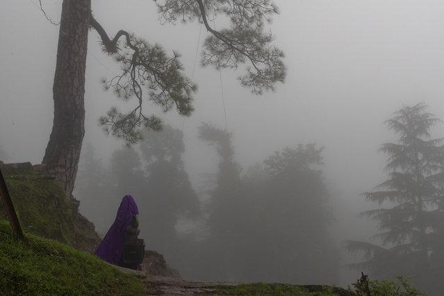 A woman walks under a thick fog in Dharmsala, India, Monday, August 10, 2020. (Photo by Ashwini Bhatia/AP Photo)