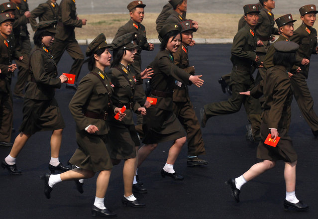 Soldiers run into a stadium to join a ceremony in Pyongyang, on April 14, 2012. (Photo by Bobby Yip/Reuters)