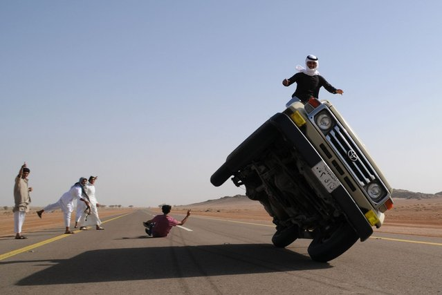 "Saudi youths demonstrate a stunt known as ""sidewall skiing"" (driving on two wheels) in the northern city of Hail, in Saudi Arabia March 30, 2013. Performing stunts such as sidewall skiing and drifts is a popular hobby amongst Saudi youths. (Photo by Mohamed Al Hwaity/Reuters)"