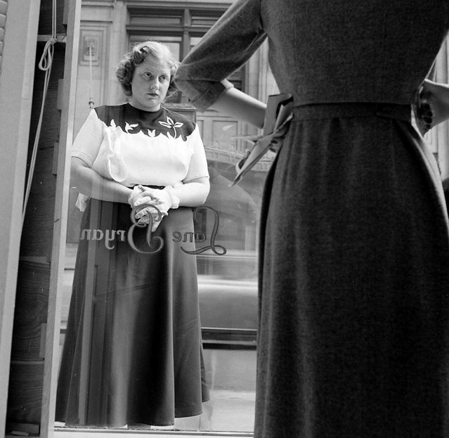 Dorothy Bradley, photographed for LIFE magazine article on obesity, eyes dress in a store window, 1949. (Photo by Martha Holmes/Time & Life Pictures)