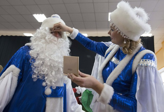 "People dressed as Father Frost, the equivalent of Santa Claus, and Snow Maiden prepare themselves for the contest ""Yolka-fest-2014"" (Fir-festival-2014) in Minsk December 12, 2014. (Photo by Vasily Fedosenko/Reuters)"