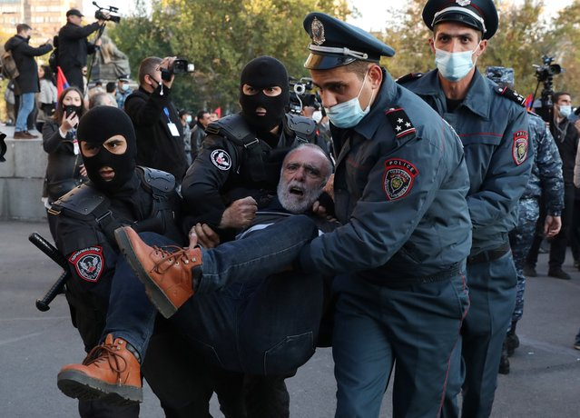 Armenian police officers detain a protestor during an opposition rally in the Freedom Square in Yerevan, Armenia, 12 November 2020. Protesters demanded the resignation of Armenian Prime Minister Nikol Pashinyan and his government. The unrest and protest erupted in Yerevan on 10 November 2020 after Armenian Prime Minister and Presidents of Azerbaijan and Russia signed a trilateral statement announcing the halt of ceasefire and all military operations in the Nagorno-Karabakh conflict zone. (Photo by Stepan Poghosyan/EPA/EFE)