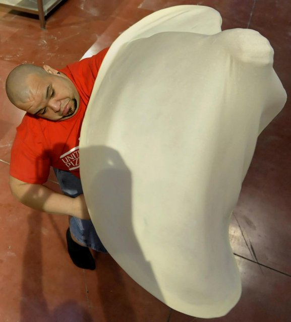 Flores Rodriguez, of Puerto Rico, performs with his dough during the freestyle event, part of the Pizza World Championships, in Parma, northern Italy, Wednesday, April 17, 2013. The 22th edition of the championships run from April 15 to April 17. (Photo by Marco Vasini/AP Photo)
