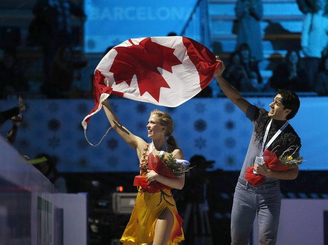 Gold medallists Kaitlyn Weaver and Andrew Poje of Canada wave their natioonal flag after winning the Ice Dance final competition at the ISU Grand Prix of Figure Skating final in Barcelona December 13, 2014. (Photo by Gustau Nacarino/Reuters)
