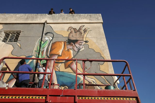 Jordanian artist, Yazan Mesmar, works on his mural on a building as part of the Baladk festival, which includes murals across Amman all with a message encouraging people to protect the environment, Jordan, October 13, 2020. (Photo by Muhammad Hamed/Reuters)