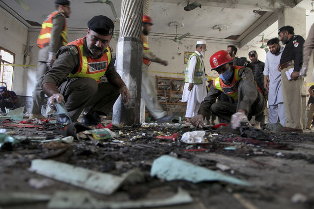 Pakistani rescue workers and police officers examine the site of a bomb explosion in an Islamic seminary, in Peshawar, Pakistan, Tuesday, October 27, 2020. A powerful bomb blast ripped through the Islamic seminary on the outskirts of the northwest Pakistani city of Peshawar on Tuesday morning, killing some students and wounding dozens others, police and a hospital spokesman said. (Photo by Muhammad Sajjad/AP Photo)