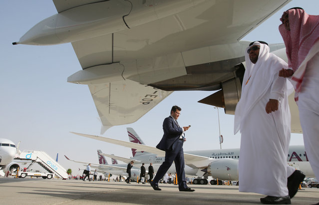 People walk around the planes during the opening of the Dubai Airshow in Dubai, United Arab Emirates, Sunday, November 8, 2015. (Photo by Kamran Jebreili/AP Photo)