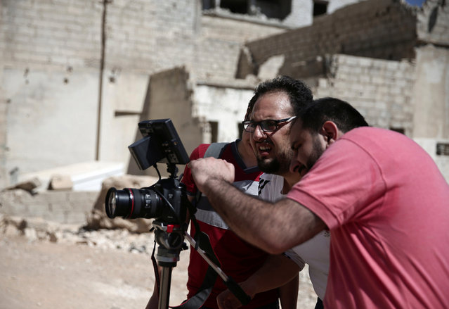 Syrian director Humam Husari (R) and cameraman Sami al-Shami (C) operate a camera as they film a scene  in the rebel-held besieged town of Zamalka, in the Damascus suburbs, Syria September 19, 2016. (Photo by Bassam Khabieh/Reuters)