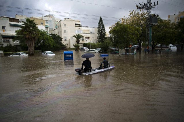 Israelis ride through a flooded street on a small motor boat in the southern city of Ashkelon, Israel, November 9, 2015. (Photo by Amir Cohen/Reuters)